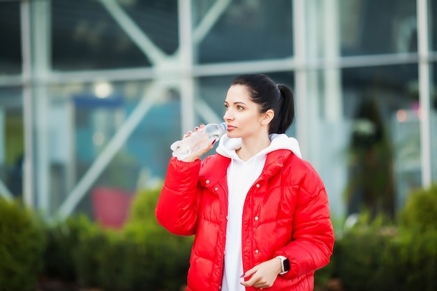 Sport im freien. frau trinkwasser nach dem laufen