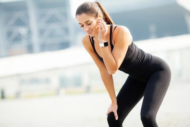 Sport im freien. hörende musik der frau am telefon beim draußen trainieren