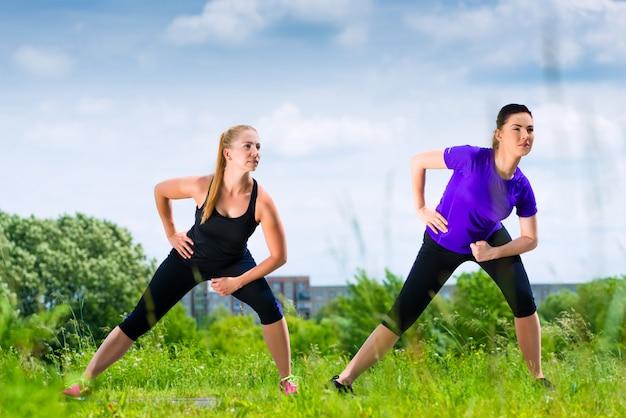 Sport im freien - junge frauen, die eignung im park tun