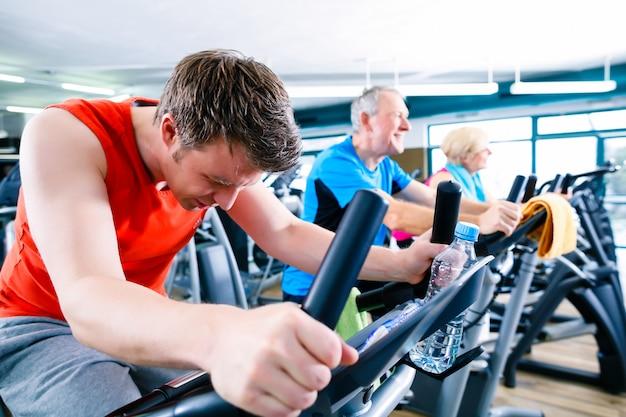 Sport in der turnhalle - menschen drehen sich mit fitness-bikes