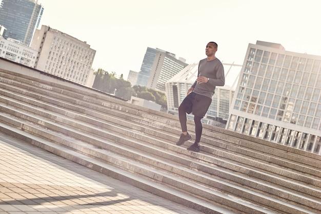 Sport in meinem leben in voller länge porträt eines athletischen afrikanischen mannes in sportbekleidung, der nach unten joggt