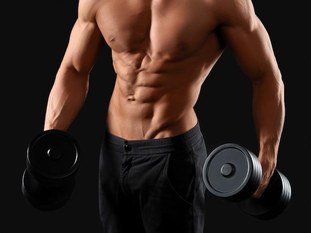 Sport ist ein lebensstil. beschnittene studioaufnahme eines zerrissenen mannes, der mit hanteln auf schwarz trainiert