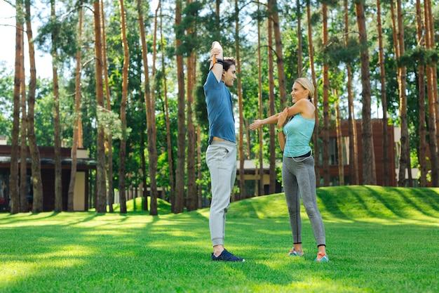 Sport ist leben. positive junge leute, die draußen stehen, während sie morgendliche gymnastikübungen zusammen machen