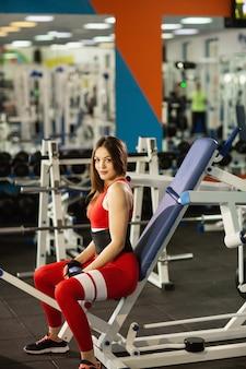 Sport jeden tag. junge gesunde frau, die an der turnhalle ausarbeitet. übungen am simulator