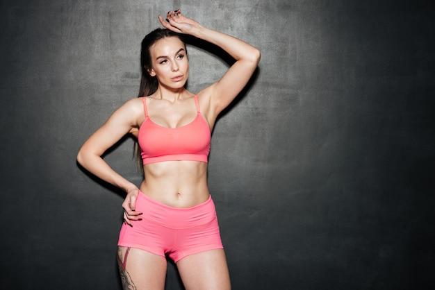 Sport junge dame stehend und posierend über schwarzer wand