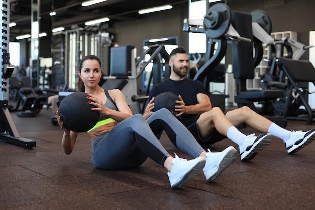 Sport junge leute, die auf einem gymnastikboden sitzen und zusammen mit einem medizinball während einer bauchübung trainieren.