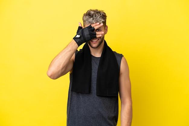 Sport kaukasischer mann isoliert auf gelbem hintergrund, der die augen mit den händen bedeckt und lächelt