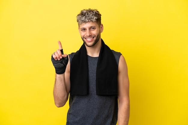 Sport kaukasischer mann isoliert auf gelbem hintergrund, der einen finger im zeichen des besten zeigt und hebt