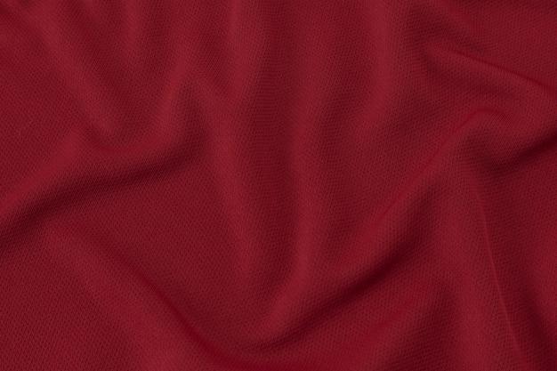 Sport-kleidungs-gewebe-beschaffenheits-hintergrund. rotes fußballtrikot