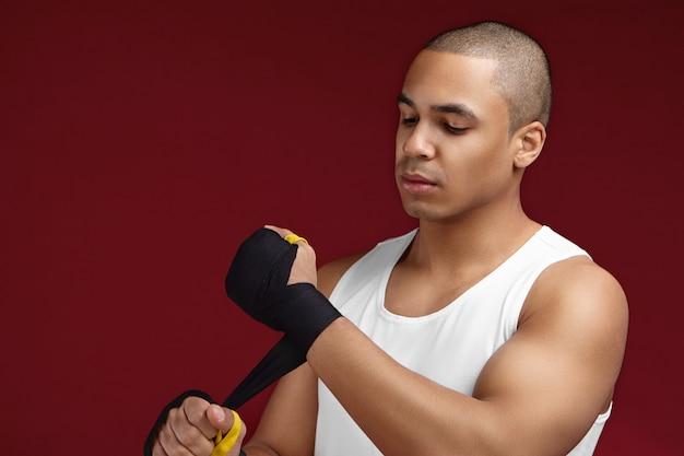 Sport-, kraft-, kraft- und motivationskonzept. porträt des hübschen jungen afroamerikanischen männlichen kickboxers, der seine fäuste für den kampf vorbereitet, schwarze boxverbände anlegt, konzentrierten blick hat