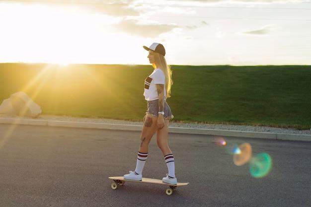 Sport-, lifestyle-, extreme- und people-konzept - schöne mädchentattoos, die bei sonnigem wetter longboard auf der straße in der stadt reiten. porträt-hipster-mädchen, das bei sonnenuntergang mit einem longboard lächelt.