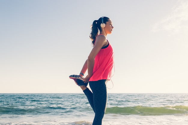 Sport mädchen am strand in kopfhörer macht sportübungen am morgen