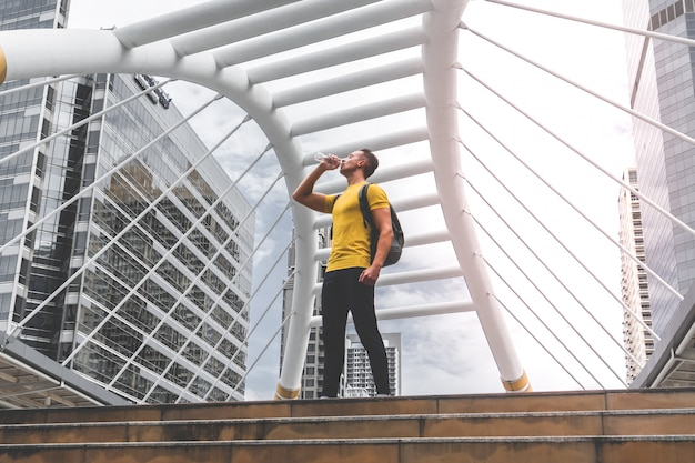 Sport mann trinkt wasser in einer pause von seiner arbeit aus
