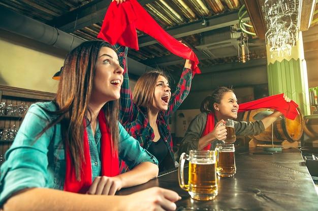 Sport, menschen, freizeit, freundschaft, unterhaltungskonzept - glückliche fußballfans oder gute junge freunde, die bier trinken und den sieg in der bar oder im pub feiern. konzept der menschlichen positiven emotionen