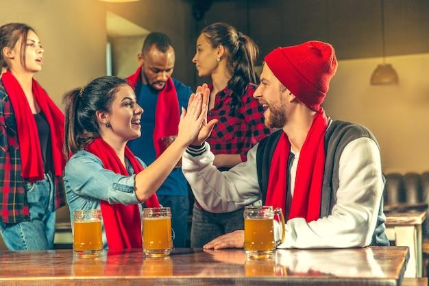 Sport-, menschen-, freizeit-, freundschafts- und unterhaltungskonzept - glückliche fußballfans oder männliche freunde, die bier trinken und den sieg in der bar oder im pub feiern