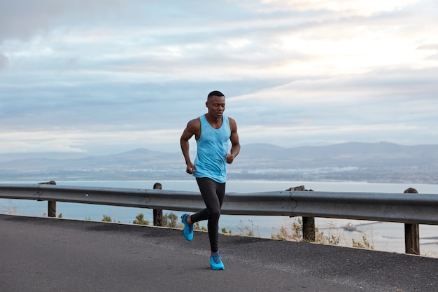 Sport-, motivations- und erholungskonzept. aktiver männlicher sportlicher schwarzer jogger läuft gegen wolkenlosen himmel in der autobahn, trägt freizeitweste und blaue sportschuhe, hat bizeps an den armen, übungen im freien.