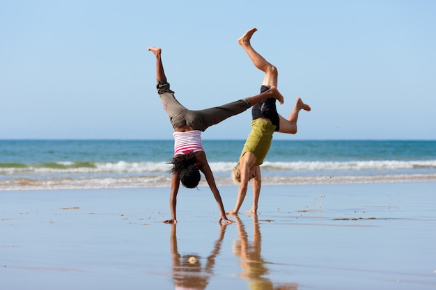 Sport paar gymnastik am strand zu tun