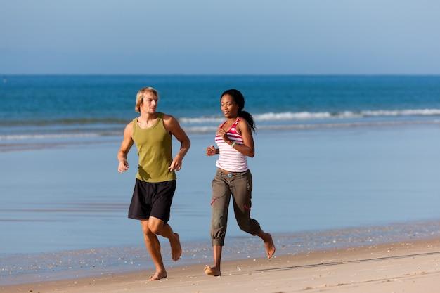 Sport paar joggen am strand