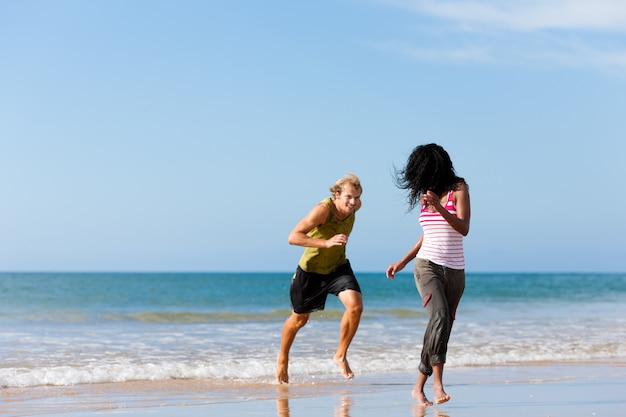 Sport paar spielen am strand