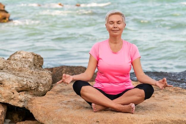 Sport reife frau am strand machen meditationsübungen.