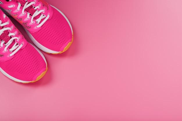Sport rosa turnschuhe auf einem rosa hintergrund mit freiem platz. draufsicht, minimalistisches konzept