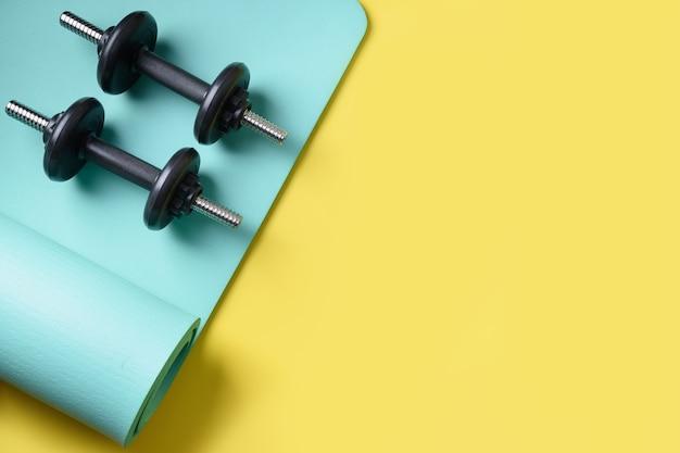 Sport schwarze hanteln auf türkisfarbener yogamatte auf gelb. speicherplatz kopieren. von oben betrachten.