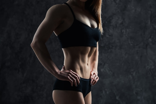 Sport sexy frau mit großem muskelbauch in einer schwarzen sportbekleidung