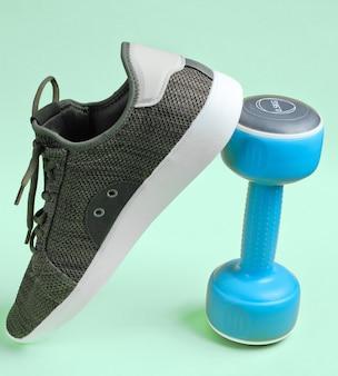 Sport sneaker und hantel auf blau.