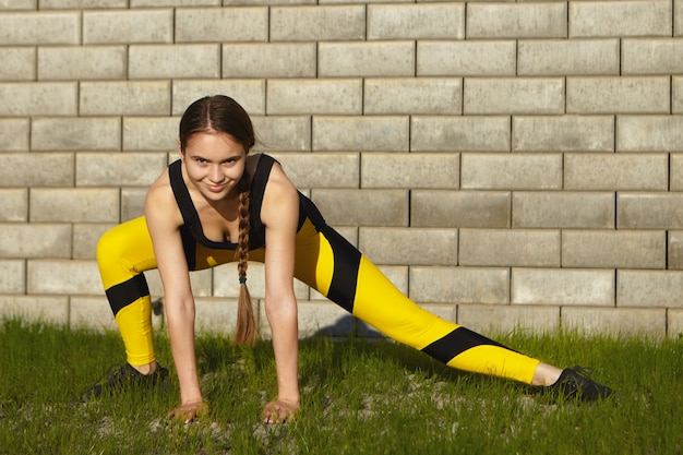 Sport, sommer, fitness und gesundes aktives lifestyle-konzept. modische athletische junge kaukasische frau mit langem zopf, der muskeln auf grünem gras streckt, seitliche ausfallschritte macht, selbstbewussten blick hat