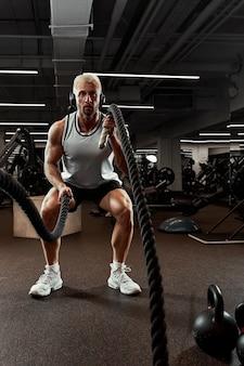 Sport. starker mann, der mit kampfseilen im fitnessstudio trainiert. athlet macht kampfseiltraining im fitnessstudio. dramatischer sporthintergrund.