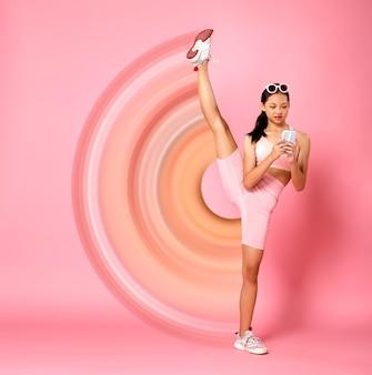 Sport teenager-mädchen hebt ihr flexibles bein an den kopf, während sie das smartphone für das soziale netzwerk verwendet. asiatische jugendsportlerin trägt pastellrosa fitness-stoffhosen über rosafarbenem hintergrund in voller länge full