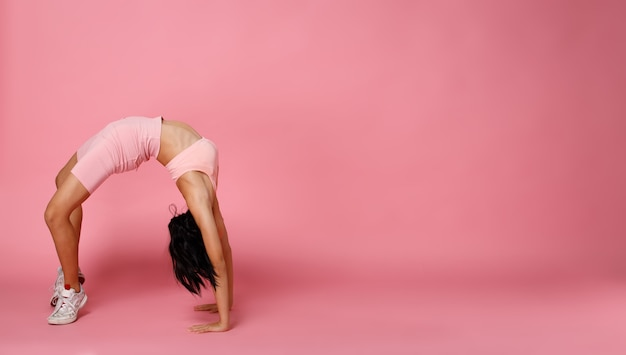 Sport teenager-mädchen üben übungsbrücke backbend, machen mode-power-posen. 12 jahre altes asiatisches jugendsportlerkind trägt pastellrosa fitness-stoffhosen über rosafarbenem hintergrund in voller länge