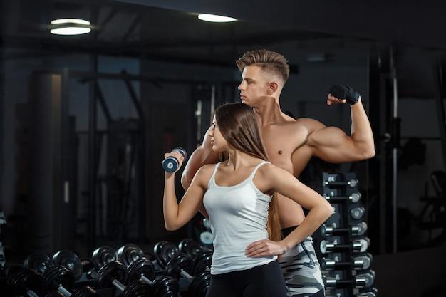 Sport, training, eignung, lebensstil und leutekonzept - junge frau mit dem persönlichen trainer, der zurück und bauchmuskeln auf bank in der turnhalle biegt