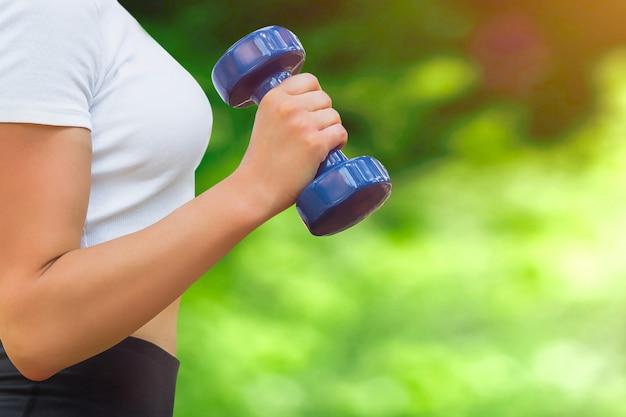 Sport-trainingskonzept. weibliche hand hält eine blaue hantel
