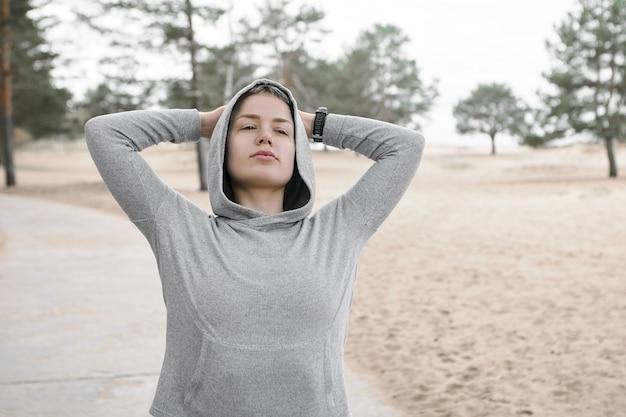 Sport und aktives lifestyle-konzept. hübsches mädchen im stilvollen kapuzenpulli, das warmen herbsttag draußen verbringt, spazieren geht oder trainiert, arme streckt, hände hinter dem kopf hält und frische luft genießt