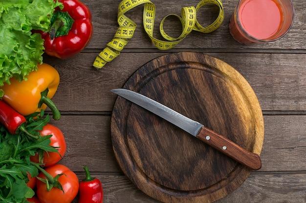 Sport- und diätgemüse ein glas tomatensaft und zentimeter paprika tomatensalat auf rustikalem ba...