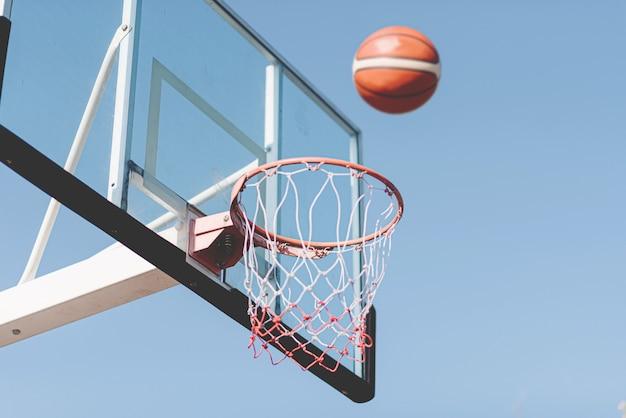 Sport- und erholungskonzept ein basketballschuss, der in die luft zu einem basketballkorb fließt.