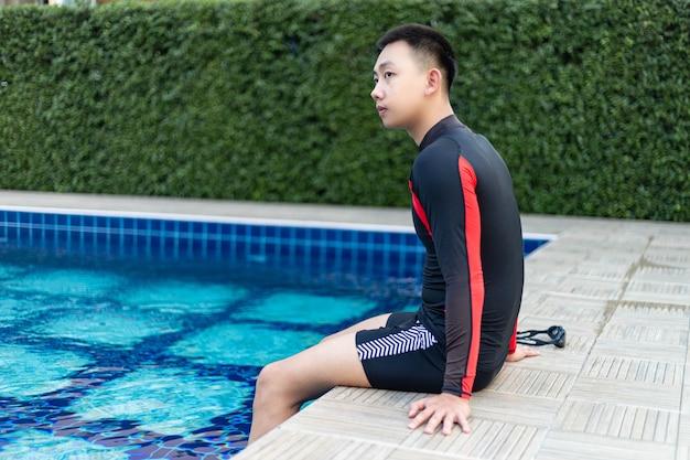 Sport- und erholungskonzept ein gut gebauter junge, der am rande eines schwimmbads mit blauem himmel sitzt und das sonnenlicht und das lebhafte wetter genießt.