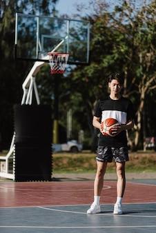 Sport- und erholungskonzept ein junger männlicher basketballspieler, der einen basketball allein im hintergrund des basketballplatzes hält.