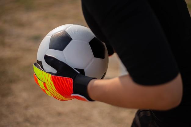 Sport- und erholungskonzept ein junger männlicher torhüter, der mit beiden händen den ball fängt, um das gegnerische team am tore zu hindern.