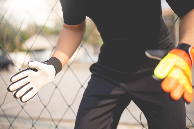 Sport- und erholungskonzept ein männlicher amateurspieler, der als torwartposition trainiert, um den ball zu fangen.