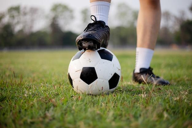 Sport- und erholungskonzept ein männlicher fußballspieler, der schwarzes t-shirt und hosen trägt und übt, den ball auf der wiese zu treten.
