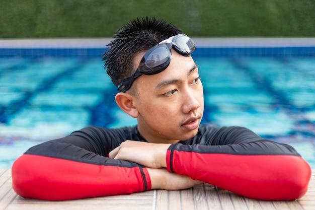 Sport- und erholungskonzept ein männlicher jugendlicher, der sein schwimmen mit übung ausruht, indem er am rand des schwimmbades hält und posiert.