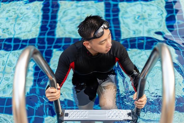 Sport- und erholungskonzept ein männlicher jugendlicher mit brille und rotem und schwarzem badeanzug, der nach dem schwimmen aus dem pool geht.