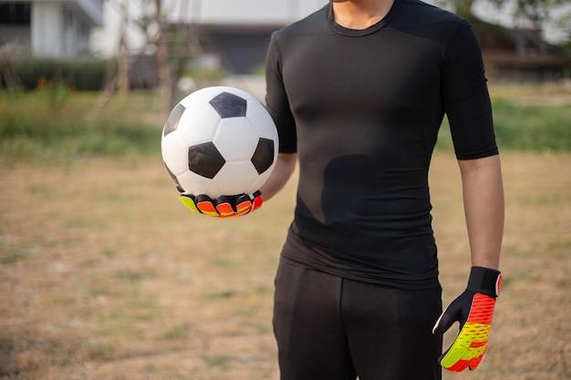 Sport- und erholungskonzept ein männlicher teenager-torhüter, der ein schwarzes outfit und ein paar bunte handschuhe trägt, die einen fußball halten.