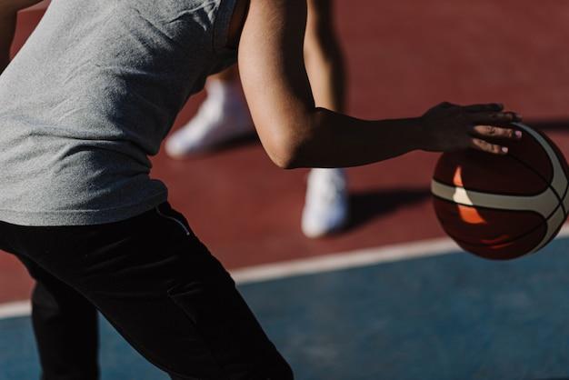 Sport- und erholungskonzept zwei männliche basketballspieler, die gemeinsam basketball auf dem sportplatz spielen.