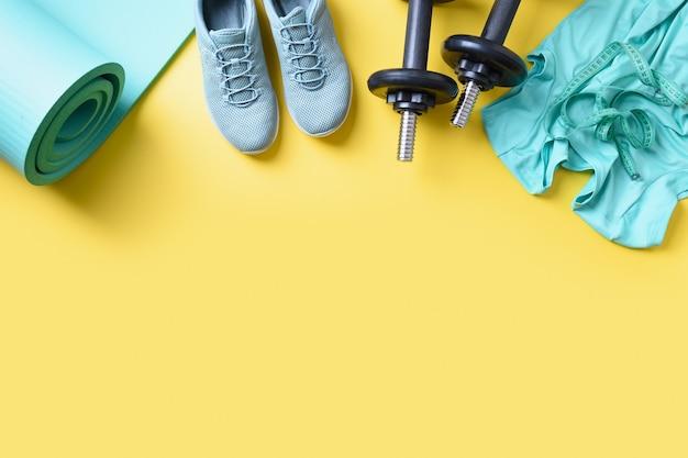 Sport- und fitnessgeräte, kurzhanteln, fitnessschuhe, maßband, yogamatte auf gelb. platz für