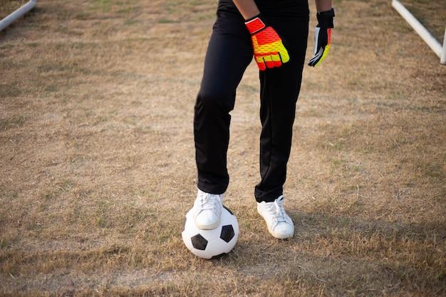 Sport und freizeit ein ball, der von einem fuß mit einem weißen turnschuh auf dem fußballplatz gestoppt wurde.