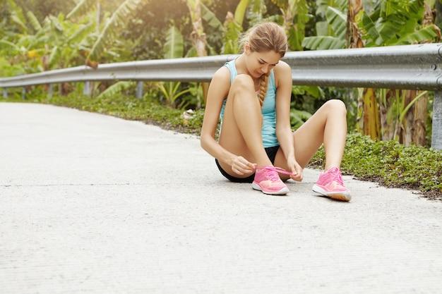 Sport und gesunder lebensstil konzept. junges sportliches mädchen, das auf der straße sitzt, die ihre rosa turnschuhe während der joggingübung im freien schnürt.