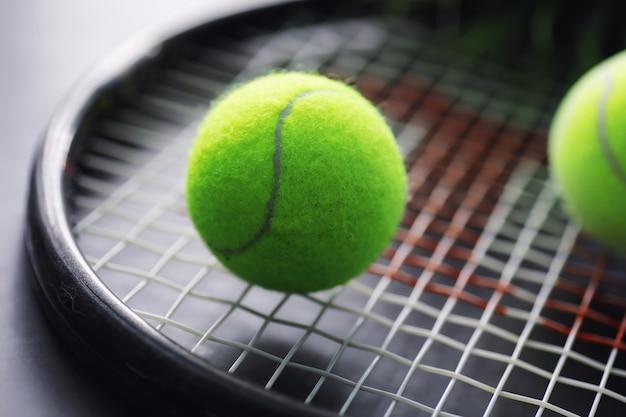 Sport und gesunder lebensstil tennis gelber ball für tennis und ein schläger auf dem tisch